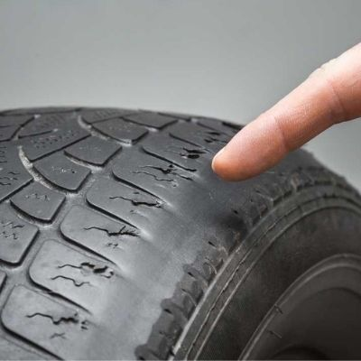man points finger at part worn tyre with shoulder wear
