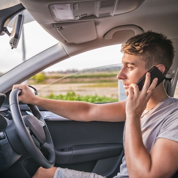 Man on mobile phone driving car