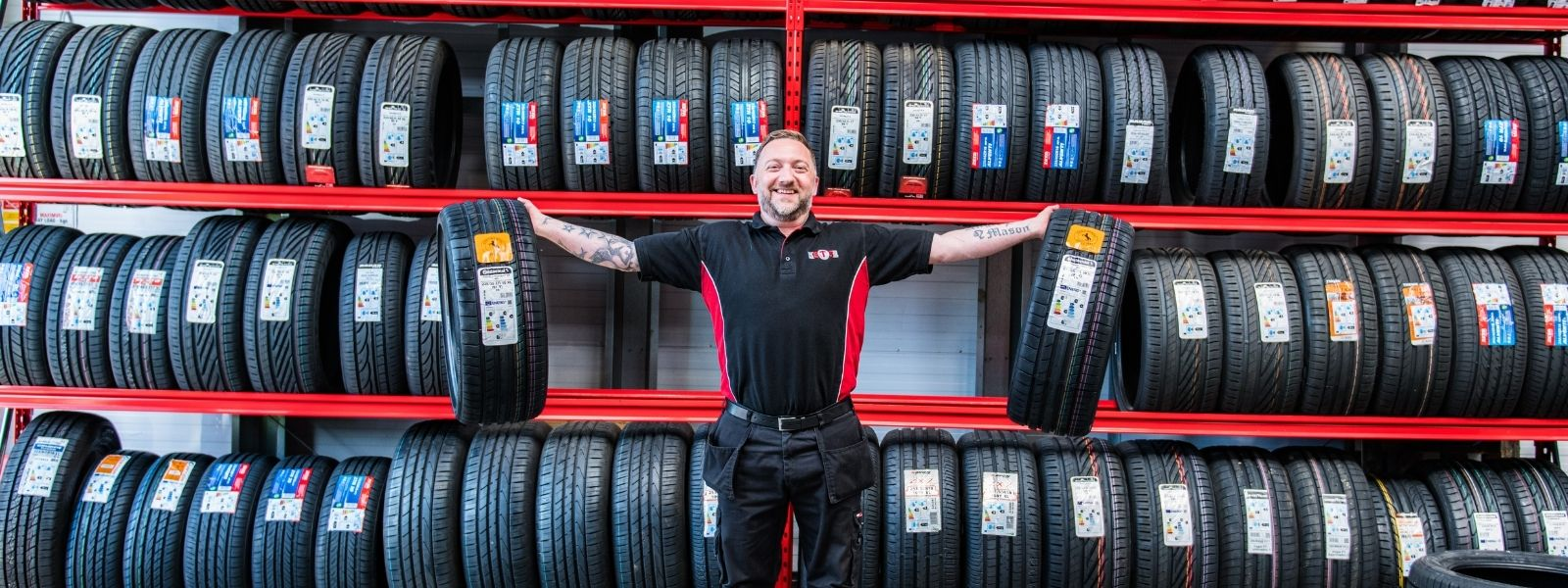 Tyre fitter standing in front of tyre racking